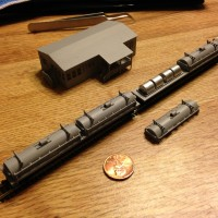 2 primed coil cars 70 foot carring four coils under each cover in z scale along with double wide frame house.