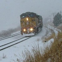 Emerging from a blinding blizzard, coal loads descend the 2% grade near Rol