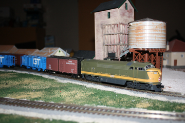 My Canadian Natonal diesel with the green and gold paint in front of my steam coaling tower and water tower. It is on the siding for the lumber company.