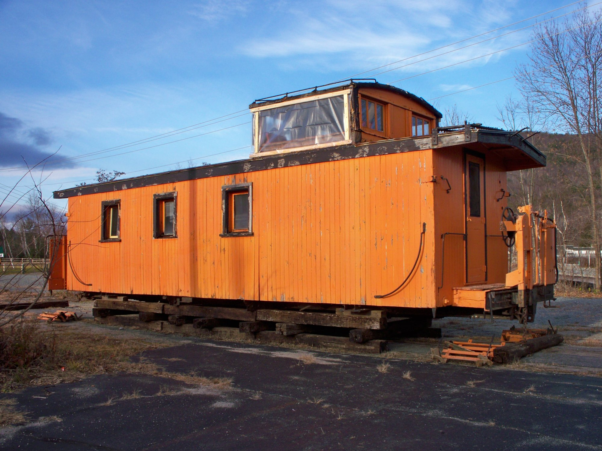 Old wooden caboose, less trucks, parked in Woodsville NH