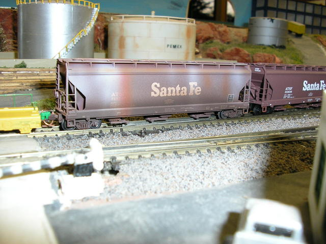 Two Santa Fe covered hoppers with elongated hatches one is weathered and other isn't